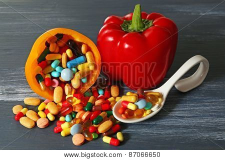 Bell-pepper and colorful pills, on wooden background