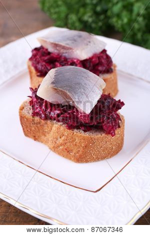 Rye toasts with herring and beets on plate close up