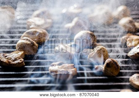 Champignon mushrooms grilled on BBQ with steam and drops of water