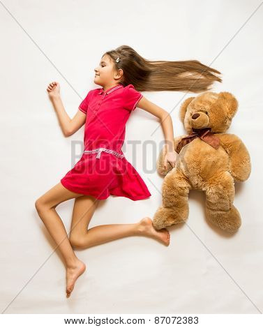 Smiling Girl Lying On Floor And Pretending To Run Fast With Teddy Bear