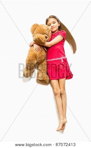 Cute Girl Lying On Floor And Hugging Big Teddy Bear