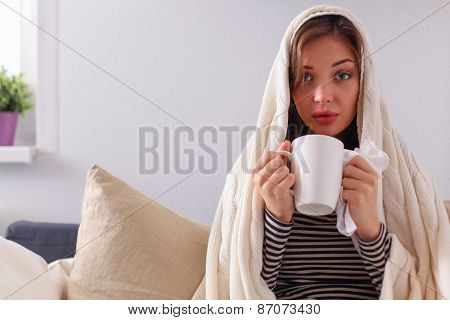 Sick woman covered with blanket holding cup of tea sitting on sofa couch