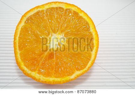 Halved Orange On A White Cardboard Close Up