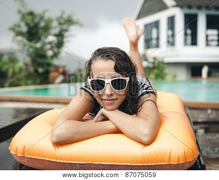 Young Woman In Bikini  Lying On An Inflatable Mattress Near The Pool