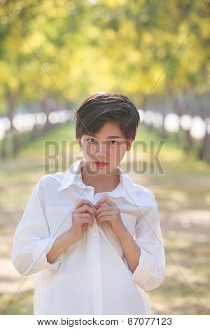 Portrait Of Beautiful Young Asian Woman Wearing White Shirts Standing In Blooming Yellow Flowers Par