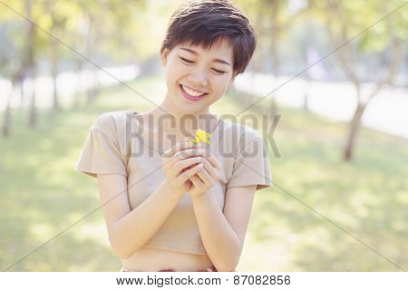 Young And Beautiful Woman Laughing To Little Flowers In Hand With Happy Face By Shallow Depth Of Fie