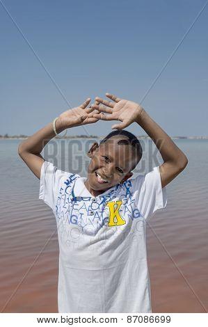Afro boy standing in front of the Retba Lake (Pink Lake)
