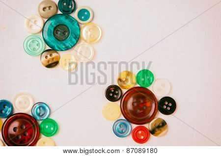 Old colored buttons for background.Laid out in the shape of a flower.