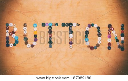 Old colored buttons laid out in the form of the word