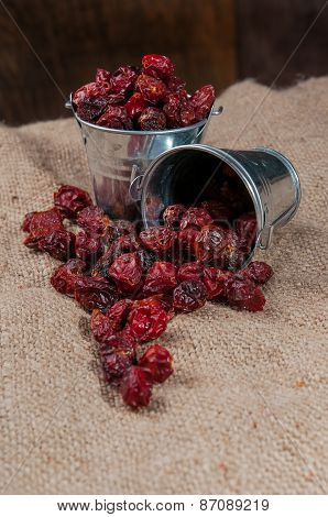 Dried rosehips in a small bucket on the sacking.