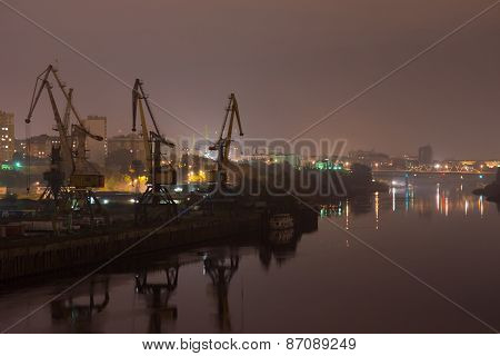 Industrial area with river port. Behind the houses, in front of water