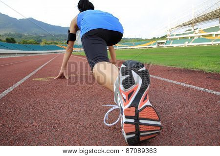 young woman runner getting ready for a run on track