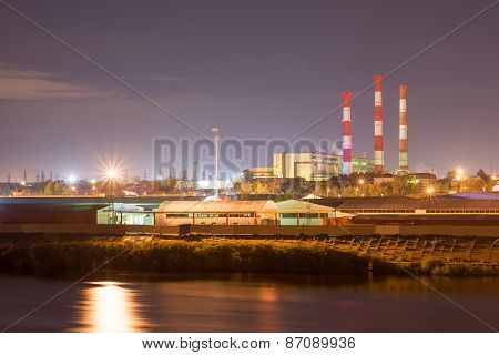 Industrial area with power plant and river port. Behind the houses, in front of water