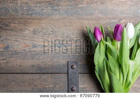 White And Lilac Tulips On A Wooden Chest