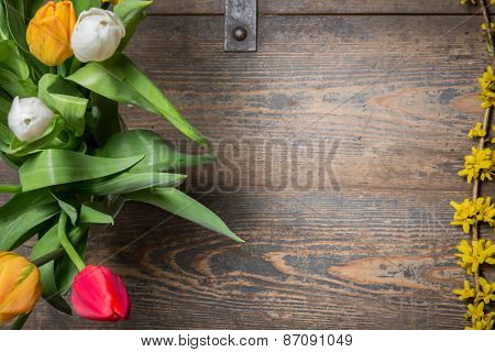 Tulips In An Vase And Flowers On A Wooden Chest