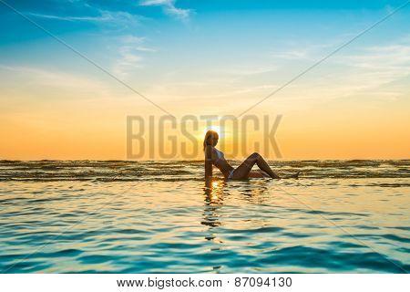 woman in white bikini posing in a sea