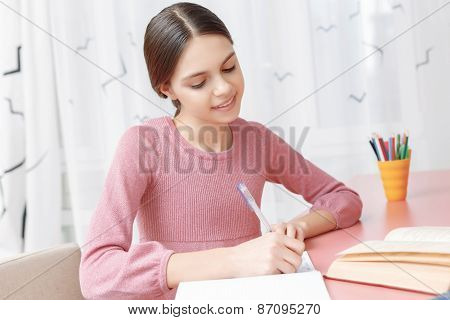 Teenage girl writing in her exercise book