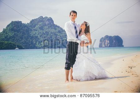 Groom Hold Bride Standing On Sandy Beach
