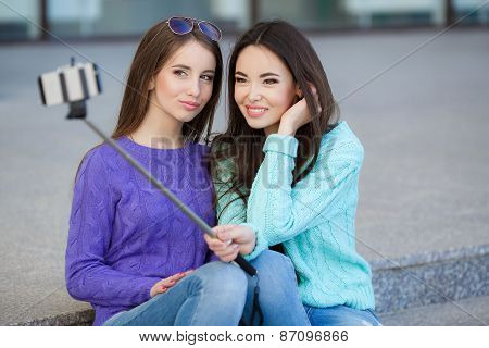 Two young attractive women are photographed with a smartphone on the streets.