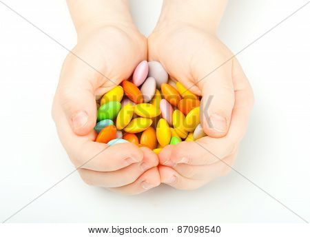 Child hands with colorful sweetmeats
