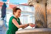 picture of fountains  - Young woman in green dress drinking water from classical fountain in the Dubrovnik city in Croatia - JPG