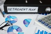 stock photo of retired  - Graphs and file folder with label  retirement plan - JPG
