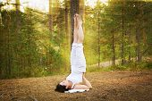 picture of shoulders  - Young woman in Yoga shoulder stand in the forest - JPG