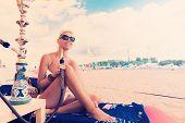foto of hookah  - Woman with hookah on the beach in bikini - JPG