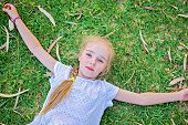 stock photo of extend  - Caucasian small girl extend your arms lying on green grass - JPG
