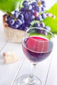 picture of merlot  - red wine in glass and fresh grape on a table