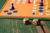 image of dice  - Horizontal photo of Two wooden dices in front of ludo with figurines - JPG