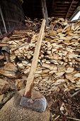 picture of ax  - Big old ax near a stack of firewood in a shed - JPG