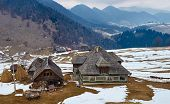 foto of household farm  - Traditional Romanian household with mountains on background on wintertime - JPG