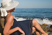 picture of beach hat  - Lady in a dark blue dress and a hat romantically looks at the sea - JPG