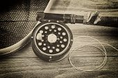 stock photo of fly rod  - Vintage concept with grain of an antique fly fishing reel rod landing net and artificial flies on rustic wood - JPG