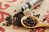 picture of pepper  - Black pepper seeds spills out of bottle Wooden spoonful of black pepper seeds - JPG