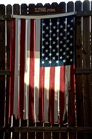stock photo of stockade  - An old tattered and worn american flag is hanging on a stockade fence backlit by morning sun with clothing optional sign above - JPG