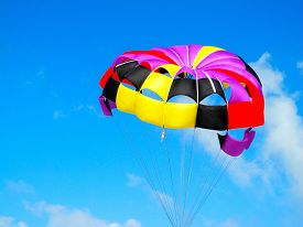 stock photo of parasailing  - Parasailing is a big thrill over the beach in Cancun - JPG