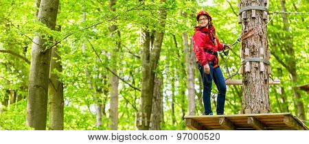 Teenager girl climbing in high rope course