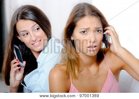 Stressed woman on the phone next to her friend