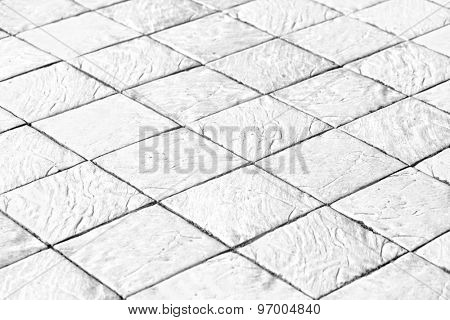 Abstract perspective background of empty textured square and flat light stucco gray and painted white pavement or plaster sidewalk outdoor. An old floor with retro style rows and dark seamless shapes.