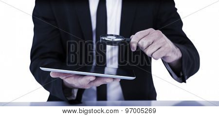 Businessman looking at his tablet through magnifying glass on white background