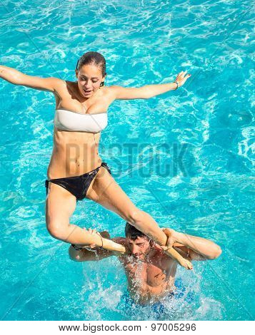 Happy Young Couple In Swimming Pool Jumping From The Shoulder - Concept Of Joyful Love And Fun