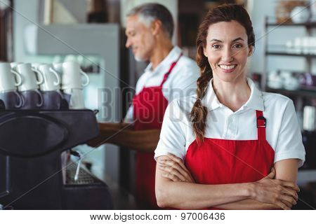 Pretty barista smiling at camera with colleague behind at the cafe