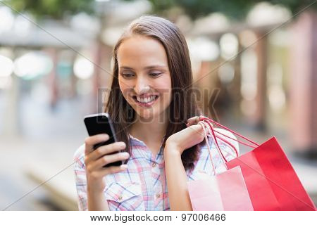 Pretty brunette using her smartphone and holding shopping bag outside