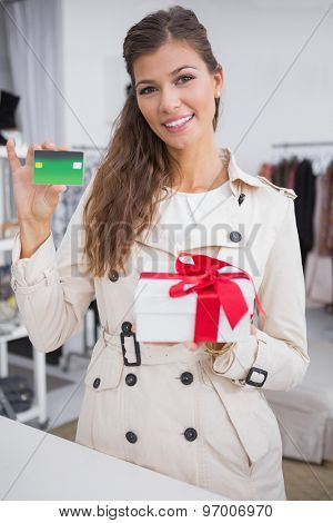 Portrait of smiling woman paying a gift by credit card at a boutique
