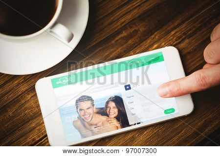 Dating website against hand using smartphone