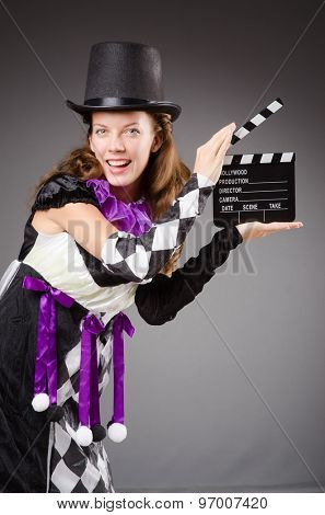 Pretty girl in jester costume holding clapperboard against gray