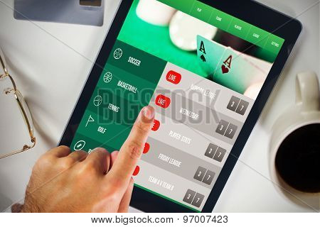 Man using tablet pc against gambling app screen