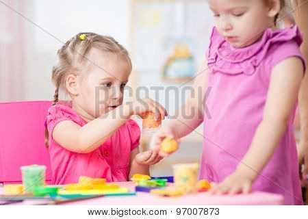Little girls playing with plasticine in school